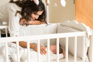 Mulher acaricia bebé no berço